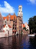 Canalside buildings and Belfry, Bruges. Royalty Free Stock Photos