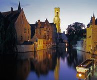Canalside buildings and Belfry, Bruges. Royalty Free Stock Images