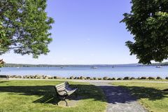 Canandaigua Lake bench in the park. View from the walking path through the park of boats on the calm blue water. Opposite shore on the horizon stock photos