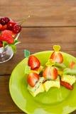 Canapé de melocotones, del kiwi y de fresas en una placa blanca Foto vertical Fotografía de archivo