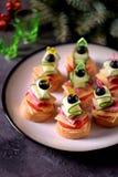 Canapé på steknålen från brödbagetten med den rostat brödost, korven, tomaten, gurkan och oliv Traditionellt mellanmål för det n Royaltyfri Foto