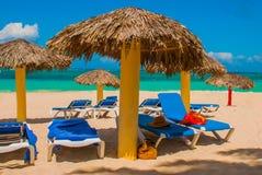 Canapés bleus du soleil avec des parapluies sur la plage Sur le fond des eaux de turquoise des Caraïbe Playa Esmeralda, Holgui Image libre de droits