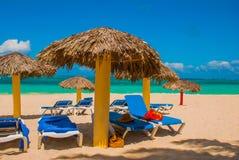 Canapés bleus du soleil avec des parapluies sur la plage Sur le fond des eaux de turquoise des Caraïbe Playa Esmeralda, Holgui Photos libres de droits