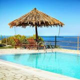 Canapés de parapluie de piscine, vue de mer photo stock