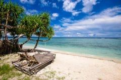 2 canapés en bambou du soleil sur un sable blanc échouent la détente par une mer tropicale Images stock