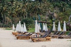Canapés en bambou sur la plage devant l'hôtel, parapluies blancs Image stock