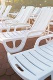 Canapés en plastique blancs sur les machines à paver en pierre de brique sur la plage au coucher du soleil Le coucher du soleil,  photo stock