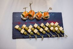 Canapés of fish, cheese and vegetables on skewers stock photo