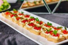 Canapе用红色鱼子酱在自助餐桌里 免版税库存照片