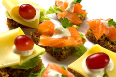 Canape. Canapé with cheese and with salmon. Garnished with red grapes, white sauce, parsley and lettuce leaves on rye bread stock image