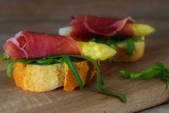 Canape with asparagus, ham and rocket salad isolated on a rustic Stock Photography