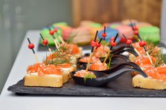Canape of bread and red fish, lie on a black stone board on the table at the banquet, wooden and glass background stock photography