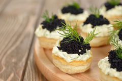 Canape with caviar. On a brown background royalty free stock photo