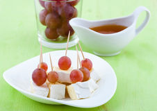 Canape from cheese and grapes. Cheese Served with grapes and honey on a plate Royalty Free Stock Photos