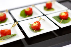 Canape cherry tomatoes cheese plate catering. Canape red cherry tomatoes cheese small plate leaf catering Royalty Free Stock Photos