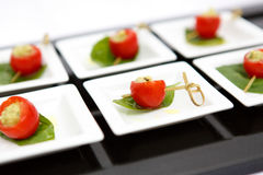 Canape cherry tomatoes cheese plate catering. Canape red cherry tomatoes cheese small plate leaf catering Stock Images