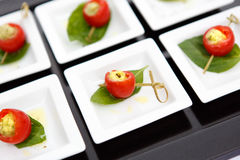 Canape cherry tomatoes cheese plate catering. Canape red cherry tomatoes cheese small plate leaf catering Royalty Free Stock Image