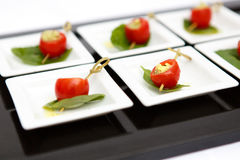 Canape cherry tomatoes cheese plate catering. Canape red cherry tomatoes cheese small plate leaf catering Stock Photos