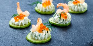 Canape d'apéritif avec le fromage rouge de caviar, de crevette et fondu sur la fin en pierre de fond d'ardoise  Photographie stock libre de droits