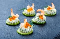 Canape del aperitivo con el caviar, el camarón y el queso cremoso rojos en el cierre de piedra del fondo de la pizarra para arrib Imagen de archivo