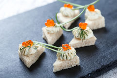 Canape del aperitivo con el caviar y el queso cremoso rojos en el cierre de piedra del fondo de la pizarra para arriba Foto de archivo libre de regalías