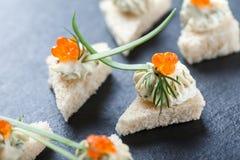 Canape del aperitivo con el caviar y el queso cremoso rojos en el cierre de piedra del fondo de la pizarra para arriba Fotografía de archivo libre de regalías