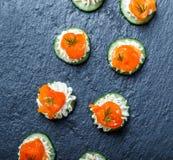 Canape del aperitivo con los salmones, el pepino y el queso cremoso en el cierre de piedra del fondo de la pizarra para arriba Foto de archivo libre de regalías