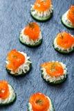Canape del aperitivo con los salmones, el pepino y el queso cremoso en el cierre de piedra del fondo de la pizarra para arriba Fotografía de archivo libre de regalías