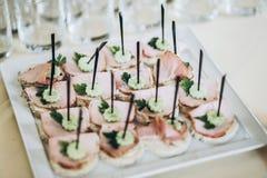 Canape delicioso de los aperitivos con el jamón y el pepino en la placa en TA Imagenes de archivo