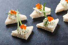 Canape dell'aperitivo con il formaggio cremoso rosso e del caviale sulla fine di pietra del fondo dell'ardesia su Fotografie Stock Libere da Diritti