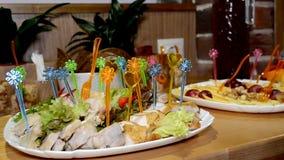 Canape della carne con gli spiedi colorati su un piatto sulla tavola di buffet archivi video