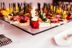 Canape differenti con carne, formaggio ed i sottaceti su una cena del buffet Fotografia Stock