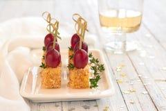 Canape met roze die druiven en kaas in een noot, op houten s wordt gepaneerd Stock Afbeeldingen