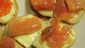 Canape mit Butter, Forelle und rotem Kaviar auf einer weißen Platte stock video