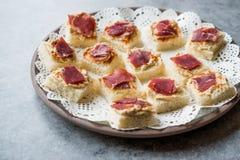 Canape mit Pastrami/Pastirma Schinken und Hummus auf kleinem quadratischem Brot lizenzfreies stockfoto