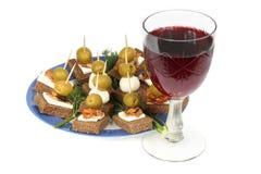 Canape och rött vin Fotografering för Bildbyråer