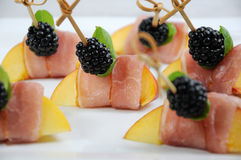 Canape of peach with jamon. Canape from peach with dried ham and blackberries Stock Images