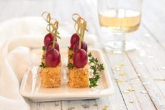 Canape with pink grapes and cheese in a nut breaded, on wooden s stock images