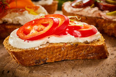 Canape with quark and fresh tomato. Seasoned with chili on sliced baguette served on a wooden board, close up view Royalty Free Stock Images