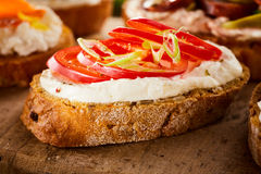 Canape with quark and fresh tomato. On a slice of crusty baguette in a bite-size appetizer served on a wooden board, low angle close up view Stock Photos