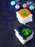 Canape with red and black caviar and wine glasses with Christmas decorations in the background Stock Images