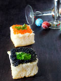 Canape with red and black caviar and wine glasses with Christmas decorations in the background stock photos
