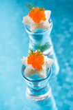 Canape with red caviar for Christmas on blue background Royalty Free Stock Photography