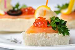 Canape with red caviar and smoked salmon. Served on plate Stock Photos
