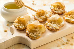 Canape with ricotta cheese, pears, nuts and honey Stock Photos