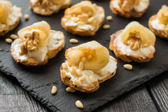 Canape with ricotta cheese, pears, nuts and honey. Canape or crostini with toasted baguette, ricotta cheese, pears, walnuts, nuts Siberian pine and honey on a stock image