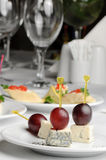 Canape with Roquefort cheese. And grape berry, served at restaurant table Stock Photography
