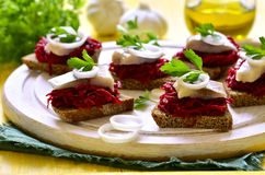Canape from rye bread with herring slice and beetroot. Royalty Free Stock Photos