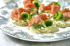 Canape with salmon,cucumber and red caviar on a curd spread. Royalty Free Stock Photos