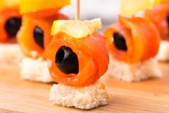 Canape with salmon and olive. Canape with delicious salmon, olive and lemon royalty free stock photos